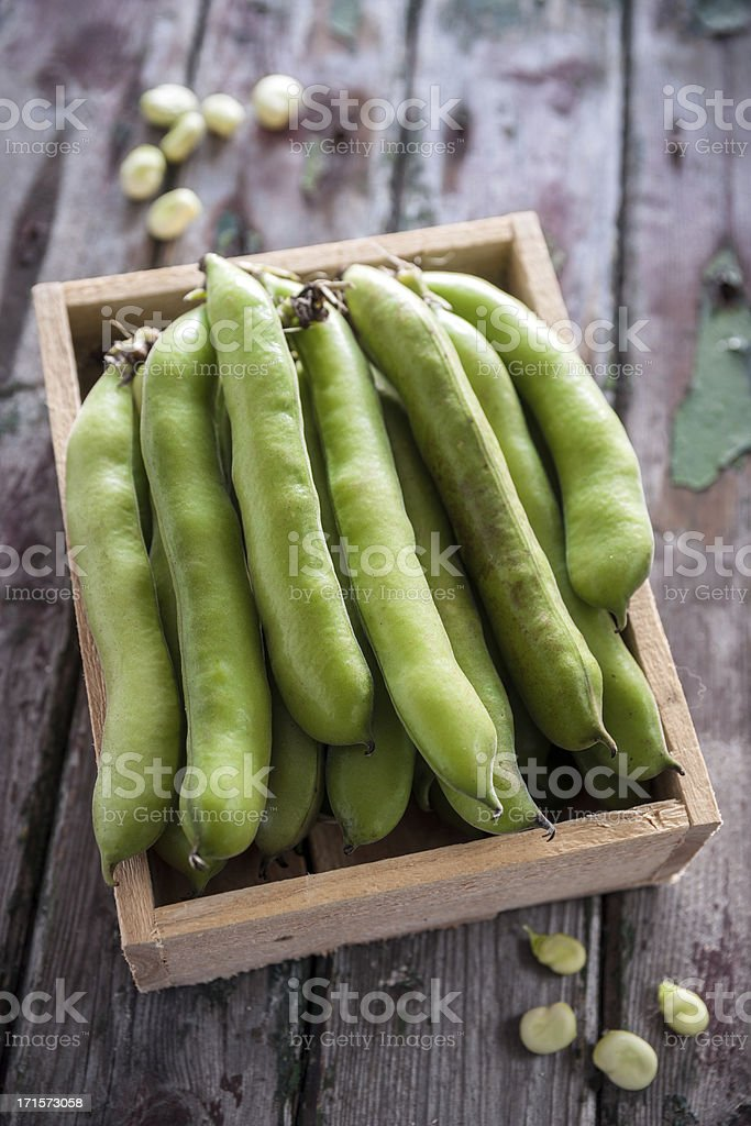 Broad beans in a wooden box on wood surface stock photo