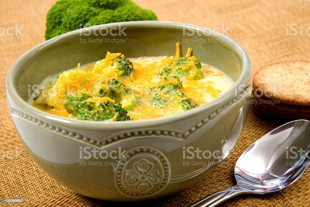 Broccoli and cheese soup in ceramic bowl on woven tablecloth stock photo