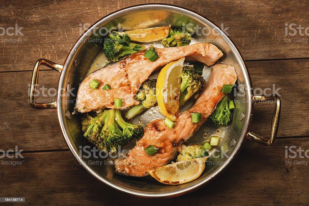 Broccoli and salmon in copper pot stock photo
