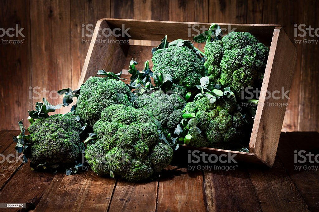 Broccoli in a crate on rustic wood table stock photo