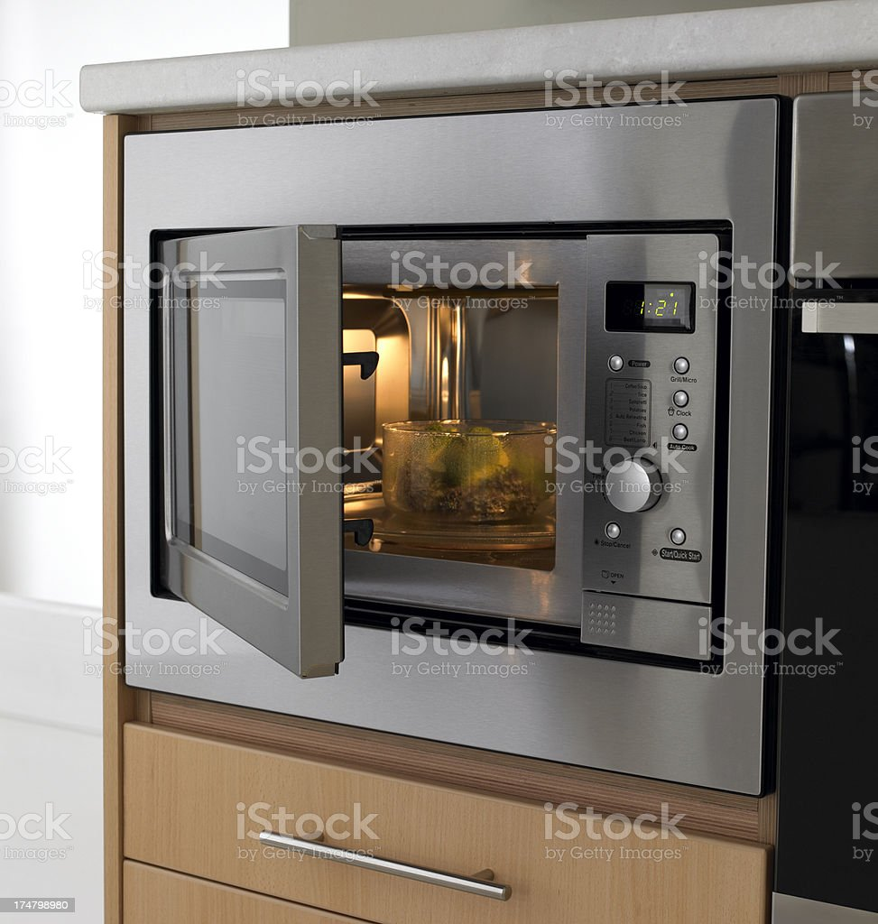 Brocolli being cooked in kitchen microwave stock photo