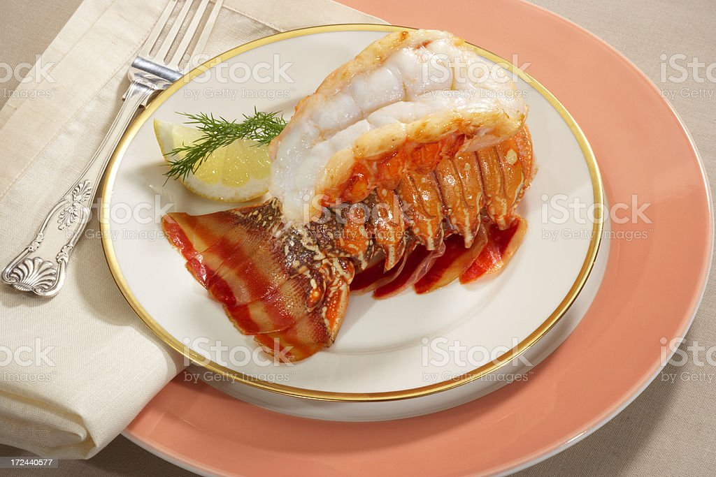 Broiled lobster tail plated with butter and herbs stock photo