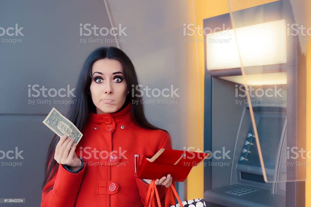 Broke Woman Holding One Dollar in Front of an ATM stock photo