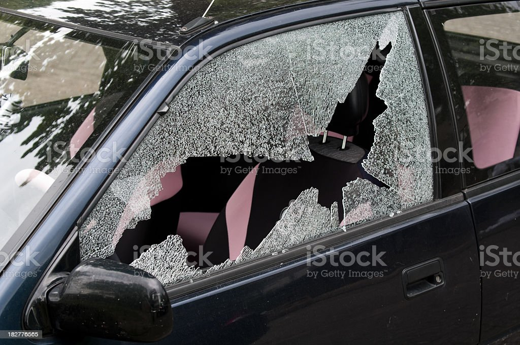 A broken and smashed window of a car in a driveway royalty-free stock photo