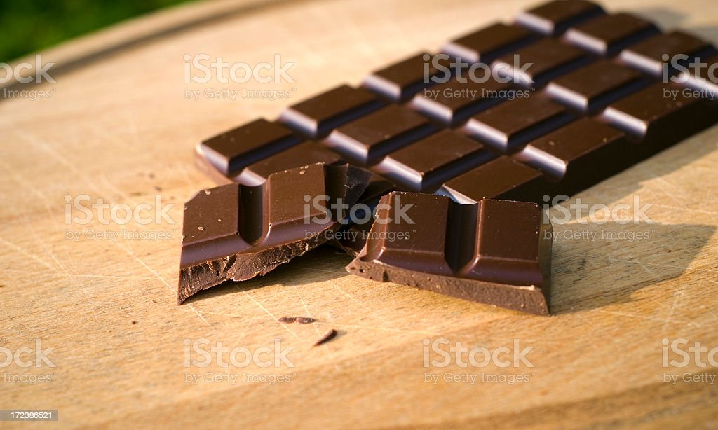 A broken bar of dark chocolate on a wooden cutting board stock photo