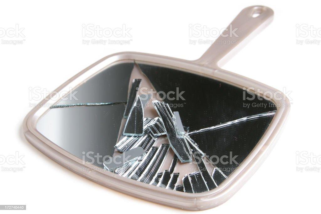 A broken beige hand held mirror on a white background stock photo