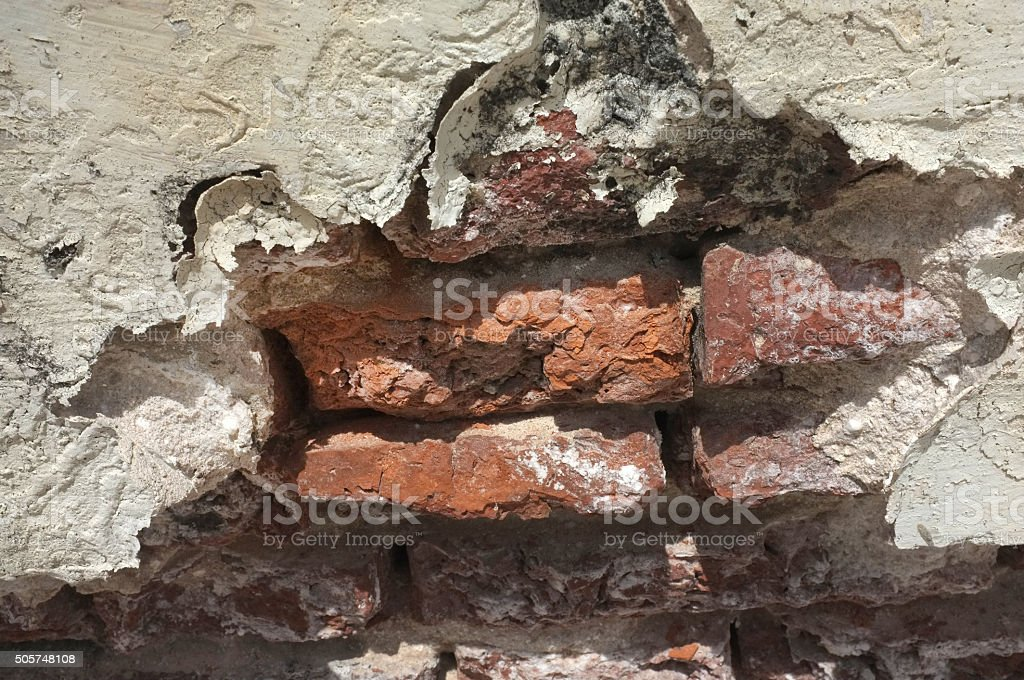 Broken brick in white wall stock photo