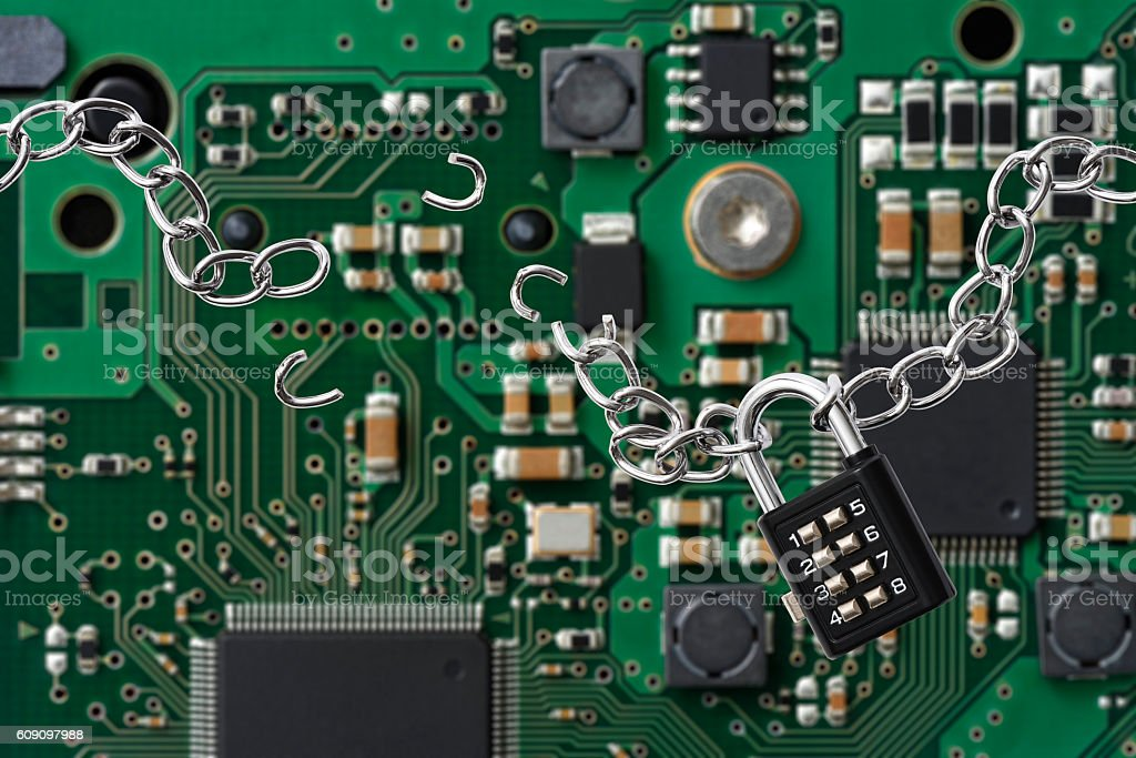 Broken chain with a combination lock against circuit board stock photo