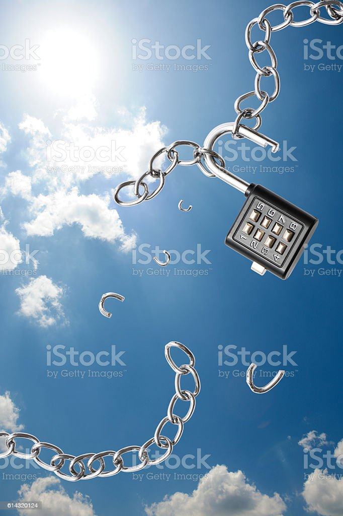 Broken chain with a unlocked combination lock against blue sky stock photo