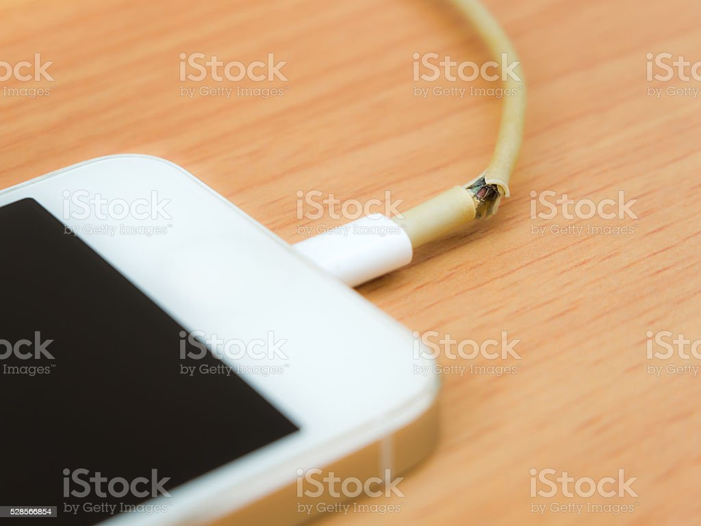 Broken charger cable with smart phone stock photo