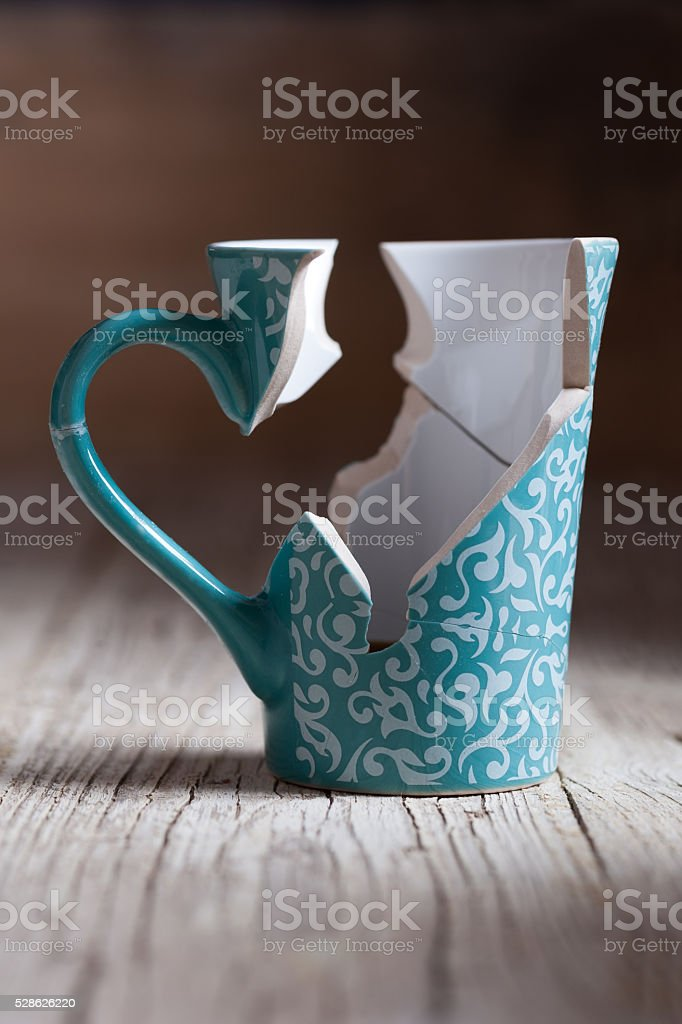 broken cup and stuck back on wooden table stock photo
