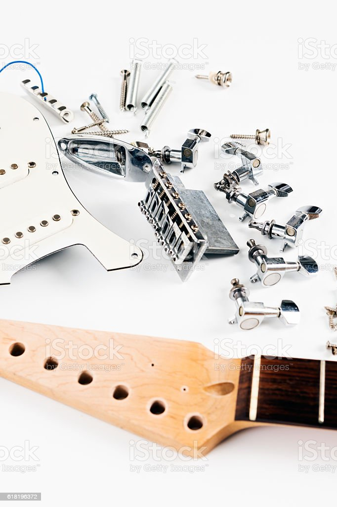 Broken electric guitar in pieces on white stock photo