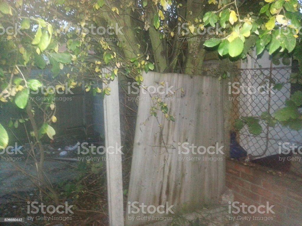 Broken fence in unkempt garden stock photo