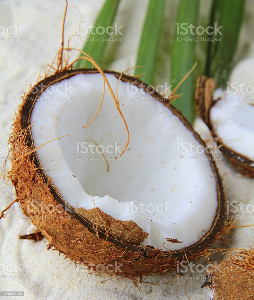 broken fresh coconut on a sandy beach royalty-free stock photo