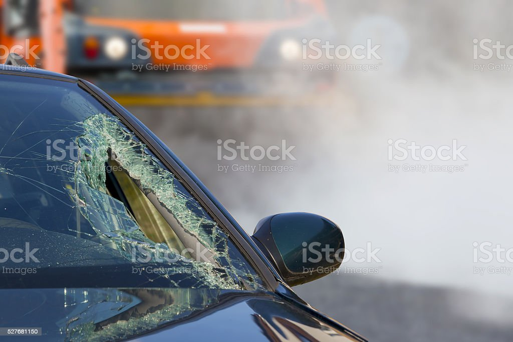 Broken glass of car in an accident and road roller stock photo
