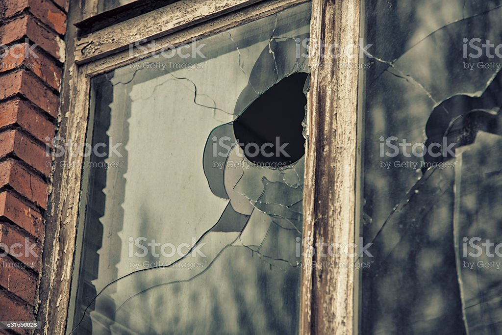 broken glass window reflecting clounding sky stock photo