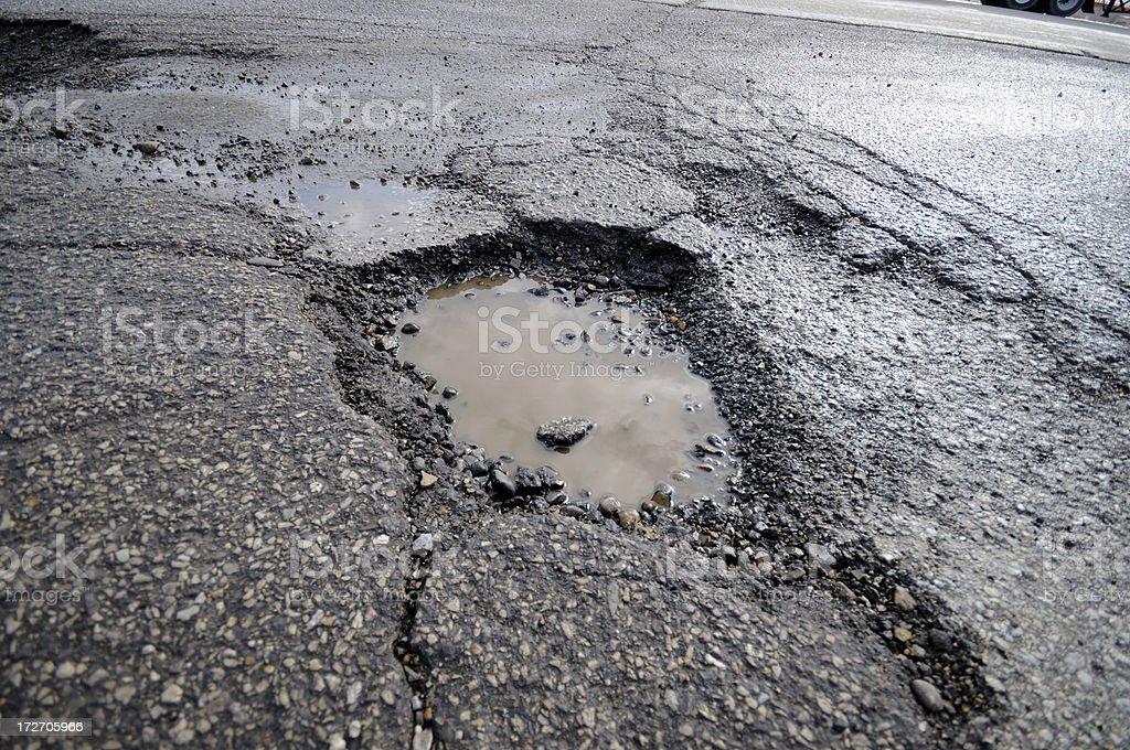 Broken gray asphalt pavement with pothole puddle stock photo