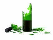 Broken green glass wine bottle on a white background