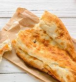broken half pita bread caucasian, lying on a cutting board