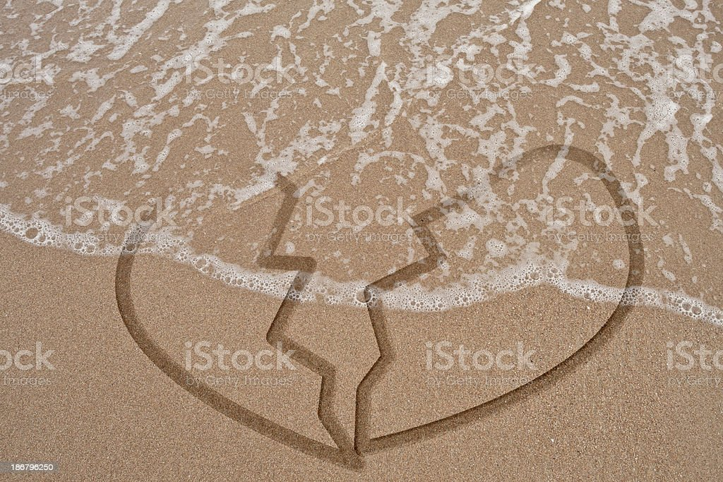 Broken heart on sand and wave royalty-free stock photo