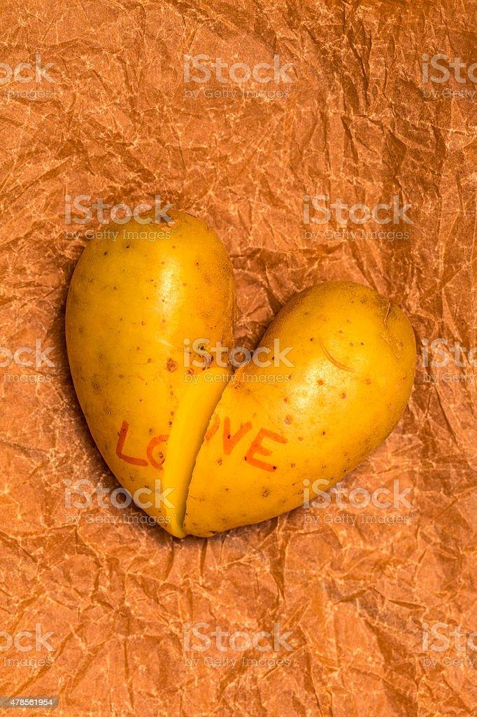 Broken heart potato on paper stock photo