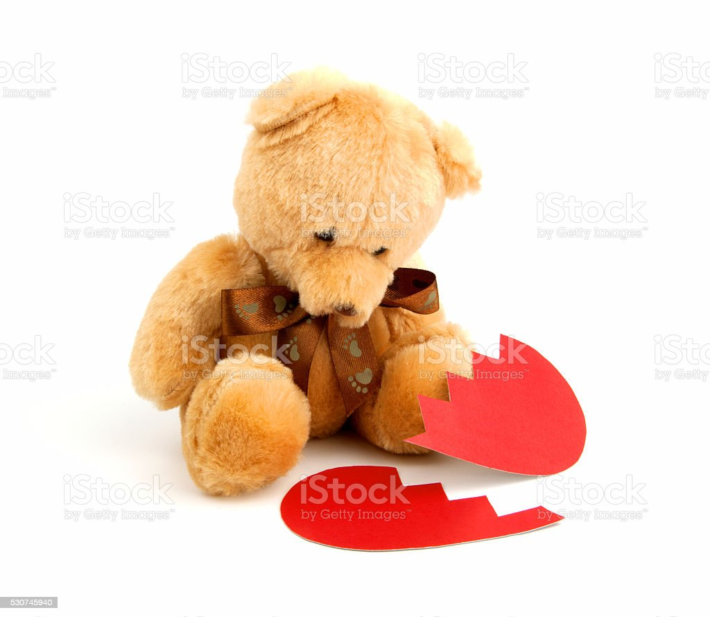 Broken heart symbolic teddy bear with Red paper heart stock photo