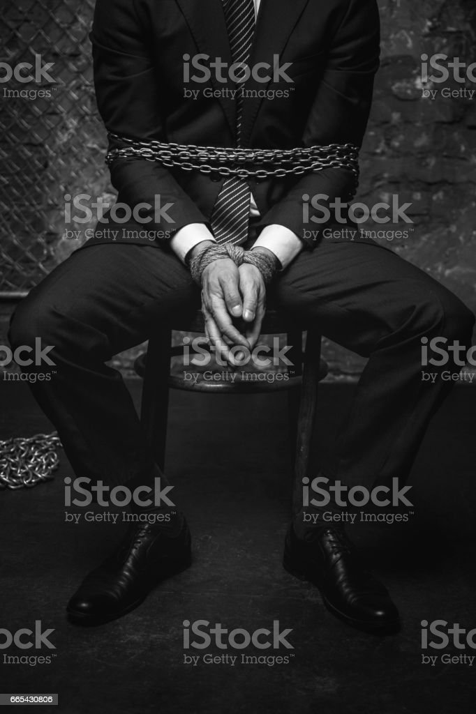 Broken helpless man tied with chains stock photo