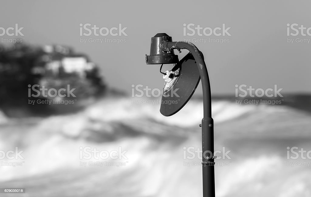 Broken lamp post by the sea stock photo