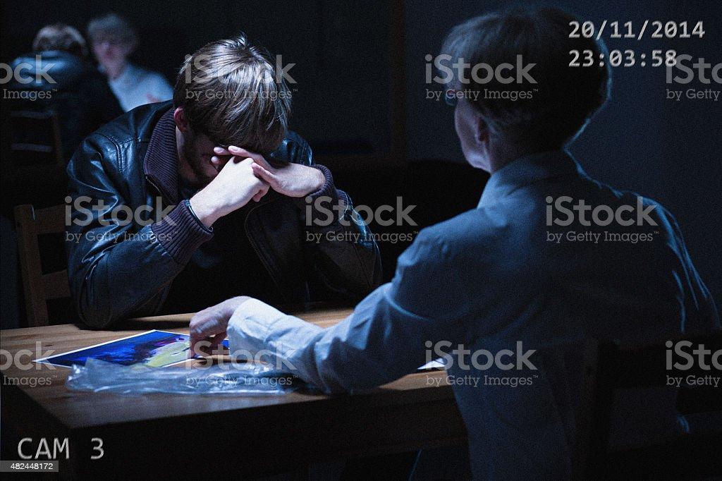 Broken man in interrogation room stock photo