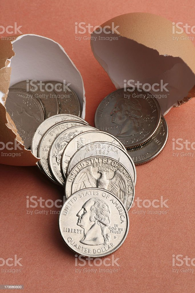 Broken Nest Egg with Money Coins Falling Out royalty-free stock photo