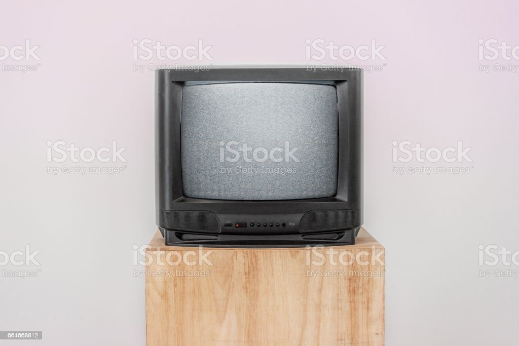 Broken old TV with screen noise on a wood shelf, Vintage object, Isolated background stock photo
