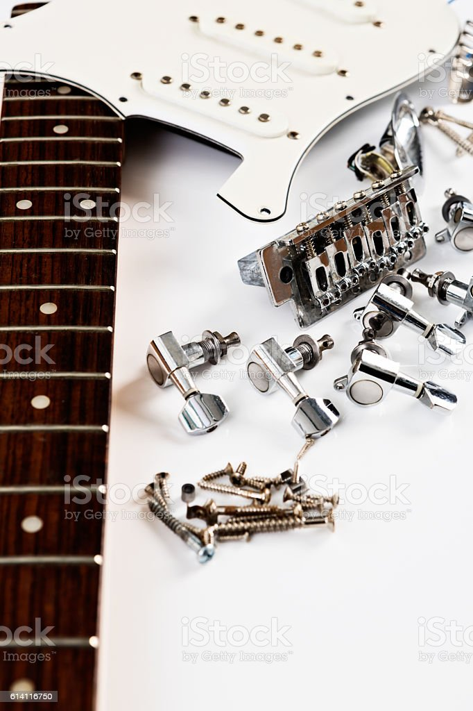 Broken or dismantled, parts of an electric guitar on white stock photo