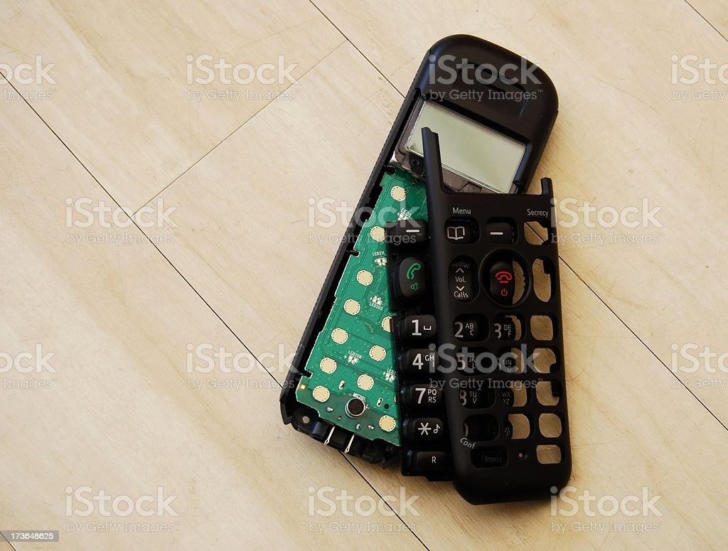 Broken phone handset on wooden floor royalty-free stock photo