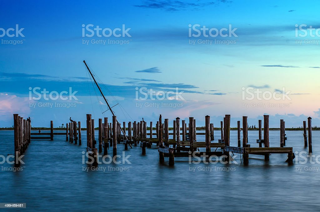 Broken pier and mast of  ship in water after sunset stock photo