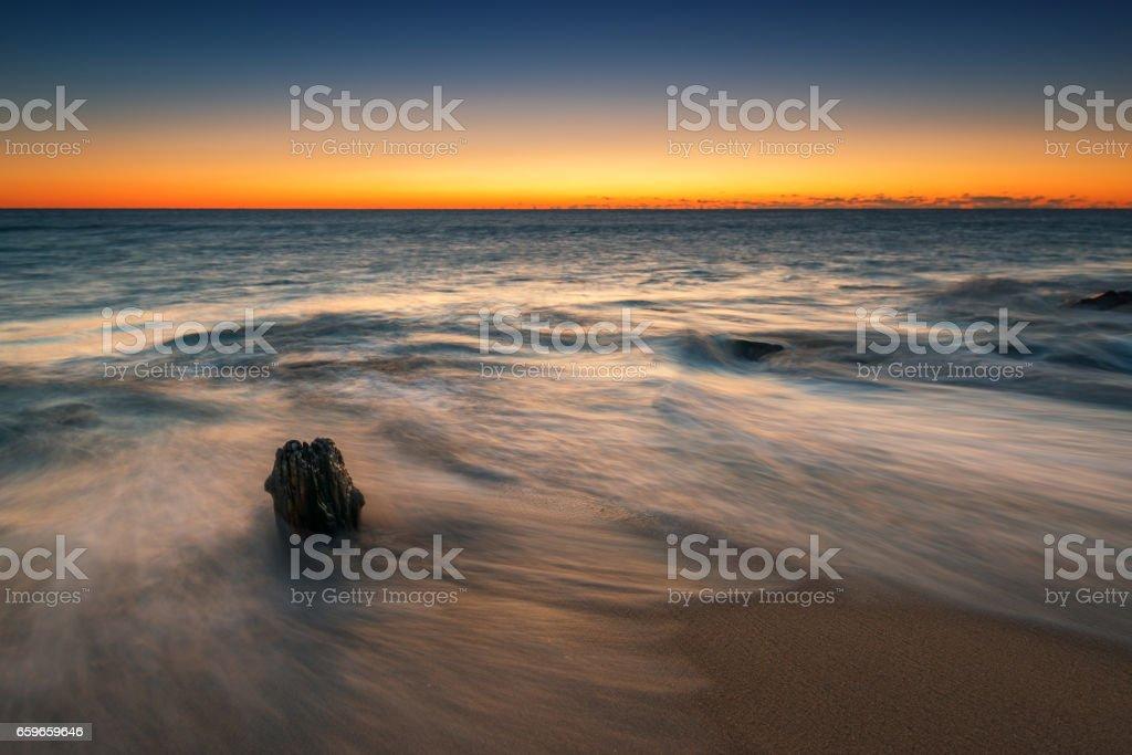 Broken piling seascape sunrise stock photo