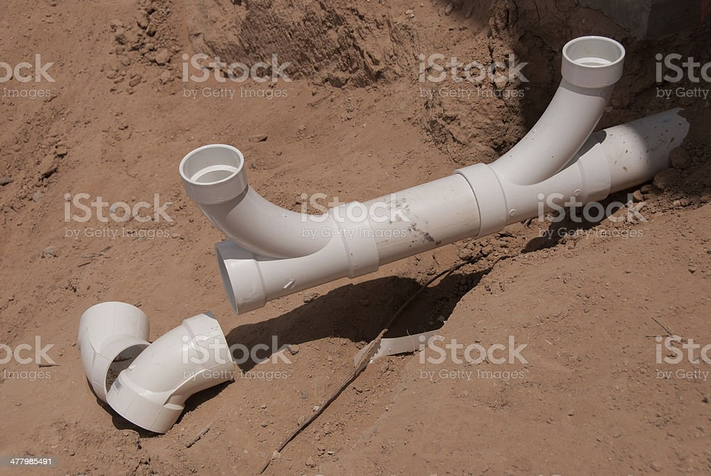 A broken PVC pipe being run out of sandy ground. royalty-free stock photo