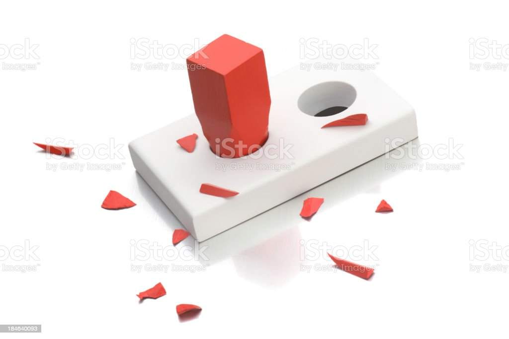 Broken red square peg going into round hole stock photo