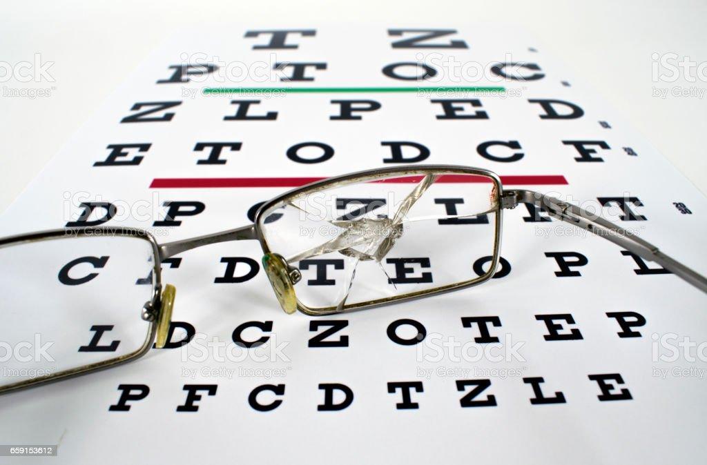 Broken Spectacles On Opticians Snellen Eye Test Chart stock photo