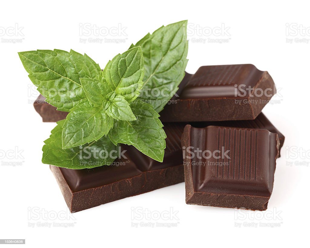 Broken squares of chocolate layered with fresh mint on top stock photo