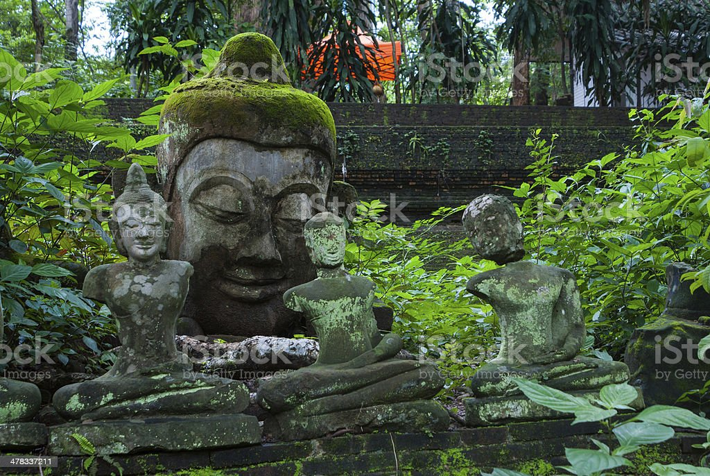Broken statues of Buddha in a forest temple royalty-free stock photo