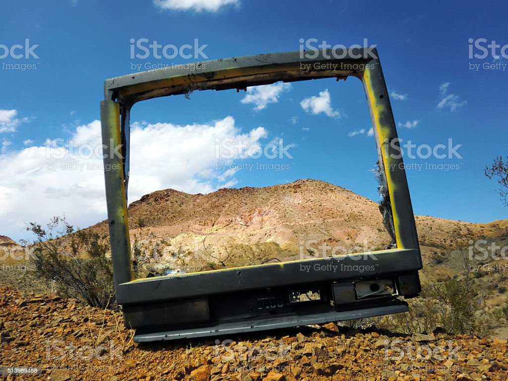 Broken television screen in desert, framing majestic mountain stock photo