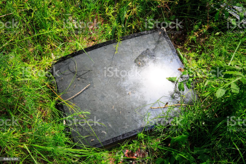 broken television tube in green grass stock photo