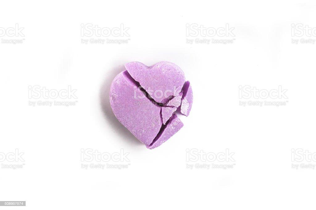 Broken Valentine's Day purple candy heart on white background stock photo