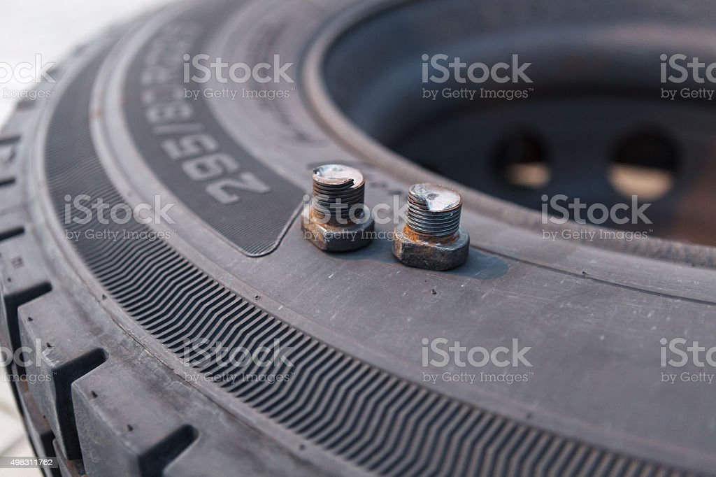 Broken wheel screws lying on bus tire stock photo