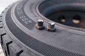 Broken wheel screws lying on bus tire
