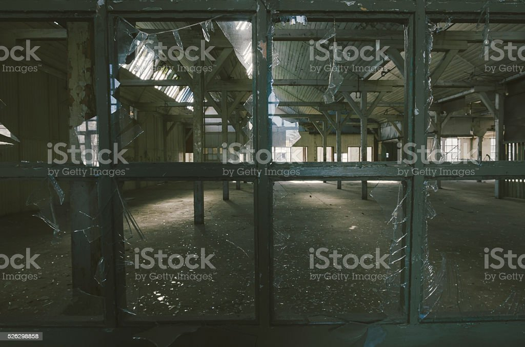 Broken windows glass in some abandoned factory hall stock photo