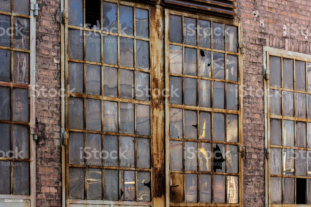 Broken windows in rusted industrial building stock photo