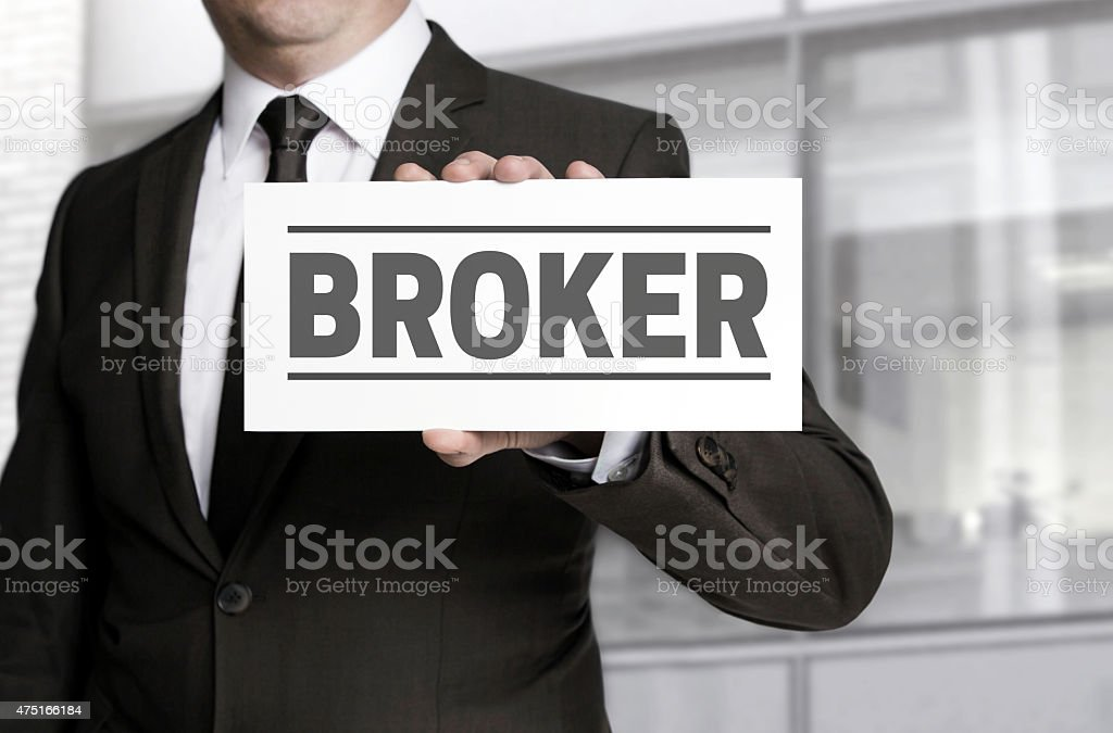 Broker sign is held by businessman. stock photo