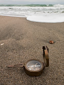 Bronze compass on the beach on sea background