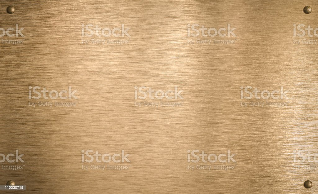 Bronze metal plate with four rivets stock photo